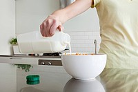 Woman pouring milk onto cereal