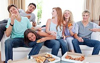 Six teenagers eating pizza in the living_room on the sofa