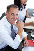 Attractive businessman in a meeting smiling at the camera