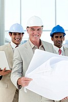 Attractive architect holding blueprints and smiling at the camera