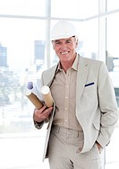 Senior architect with a hardhat holding blueprints in a building site