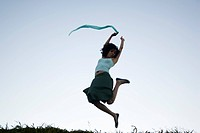 Carefree young woman leaping, scarf in hand trailing behind