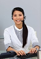 Ethnic customer service representative with headset on smiling at the camera
