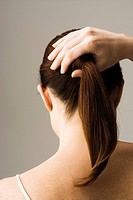 Woman styling hair, rear view