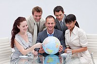 Business team holding a terrestrial globe in the office International business concept