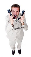 Stressed businessman yelling tangled up in phone wires against a white background