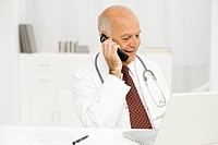 Doctor at desk on phone call