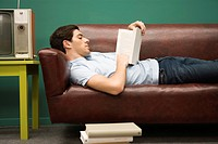 Young man relaxing on sofa with book
