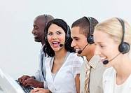Laughing businesswoman and her team working in a call center against a white background