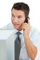 Smiling businessman on phone working at a computer
