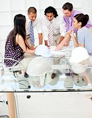 A group of architects studying plans in a meeting with hardhats on the table