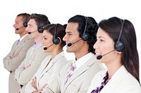 Confident business team lining up with headset on against a white background
