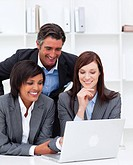 Smiling businesswomen and their colleague working at a laptop in the office