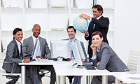 Smiling manager holding a terrestrial globe with his team working at computers Business concept