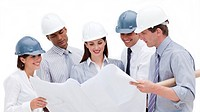 Smiling architects studying a blueprint against a white background