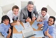 High angle of a cheerful business team with thumbs up in a meeting