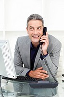 Attractive businessman on phone at his desk in the office