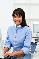 Young businesswoman working at a computer looking at the camera
