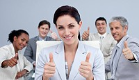 Beautiful businesswoman and her team with thumbs up in a meeting