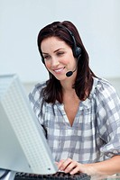 Charming businesswoman with headset on working at a computer in a call_center