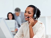 Positive businesswoman talking on headset at work