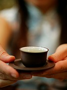 Close_up of a person´s hand holding a cup of tea with a saucer