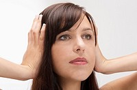 young woman refusing to hear and stopping noise by putting her fingers in her ears