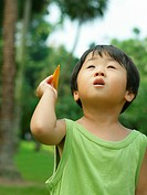 Close_up of a boy holding a paper airplane