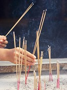 Close_up of a person´s hands holding incenses