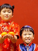 Portrait of a girl and a boy holding oranges