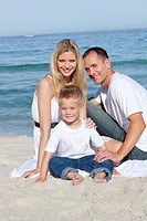 Portrait of cheerful parents with their son sitting on the sand at the beach