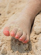 Close_up of a girl's foot in sand