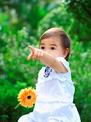 Close_up of a baby girl holding a gerbera daisy and pointing forwards