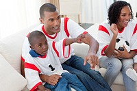 Excited Afro_American family wathing a football match on the sofa