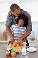 Happy father slicing bread with his son in the kitchen