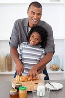 Smiling father and his son cutting bread in the kitchen