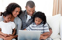 Happy Afro_American family using a laptop on the sofa