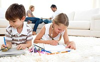 Cute siblings drawing lying on the floor in the living room