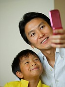 Mid adult man with his son taking a photograph of themselves with a mobile phone