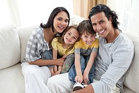 Joyful family sitting on sofa at home