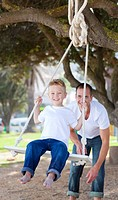 Jolly father pushing his son on a swing in a park