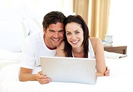 Loving couple using laptop lying on the bed