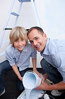 Portrait of smiling father and his son preparing paint at home