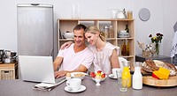 Happy couple using a laptop while having breakfast in the kitchen