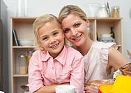 Jolly little girl eating fruit with her mother in the kitchen