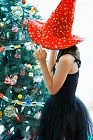 Side profile of a girl wearing a party hat and standing near a Christmas tree