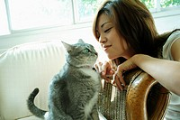 Side profile of a young woman playing with a cat