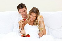 Lovers drinking Champagne with strawberries lying on their bed