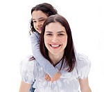 Happy mother giving her daughter piggyback ride against a white background