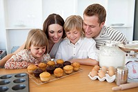 Jolly family presenting their muffins in the kitchen
